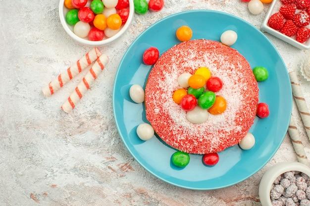 Draufsicht köstlicher rosa kuchen mit bunten süßigkeiten auf weißem boden süßigkeiten dessert farbe regenbogen goodie cake