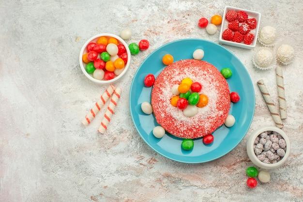 Draufsicht köstlicher rosa kuchen mit bunten süßigkeiten auf weißem schreibtisch süßigkeiten dessert farbe regenbogen goodie cake
