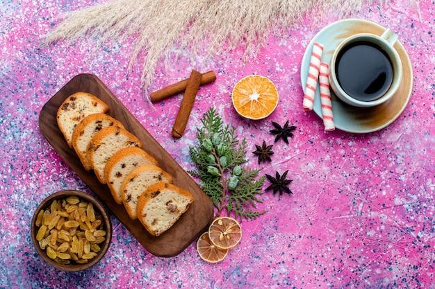 Draufsicht köstlicher rosinenkuchen geschnittener kuchen mit kaffee auf dem rosa schreibtisch backen kuchenzucker-süßer keksplätzchen