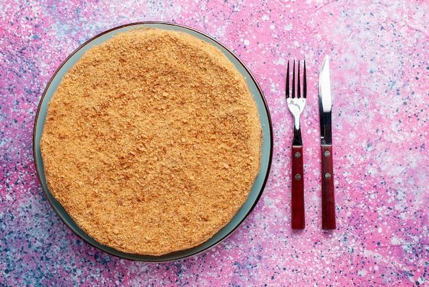 Draufsicht köstlicher runder kuchen innerhalb der glasplatte mit besteck auf dem hellen schreibtischkuchenkuchenkeks süßer backzucker