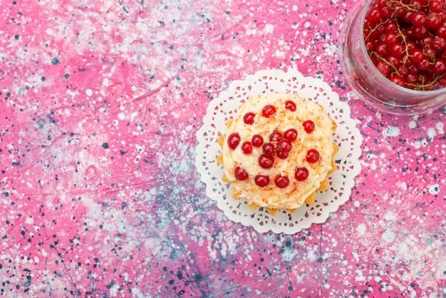 Draufsicht köstlicher runder kuchen mit sahne und frischen roten preiselbeeren auf dem lila bodenzucker