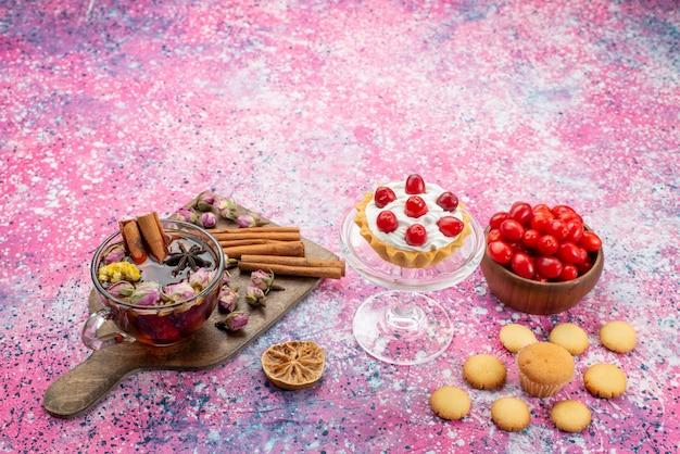 Draufsicht köstlicher sahnetorte mit frischen roten preiselbeeren zusammen mit zimtplätzchen und tee auf dem lila schreibtisch süß