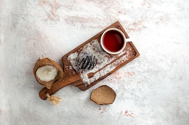 Draufsicht köstlicher schokoladenkuchen mit tasse tee auf dem hellen weißen schreibtischschokoladenkuchen-kekszucker-süßer kekstee