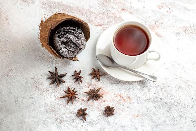 Draufsicht köstlicher schokoladenkuchen mit tasse tee auf der hellen weißen oberfläche schokoladenkuchenkeks süßer kekstee
