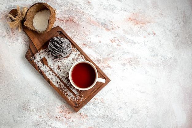 Draufsicht köstlicher schokoladenkuchen mit tasse tee auf weißem hintergrund schokoladenkuchen kekszucker süßer kekstee