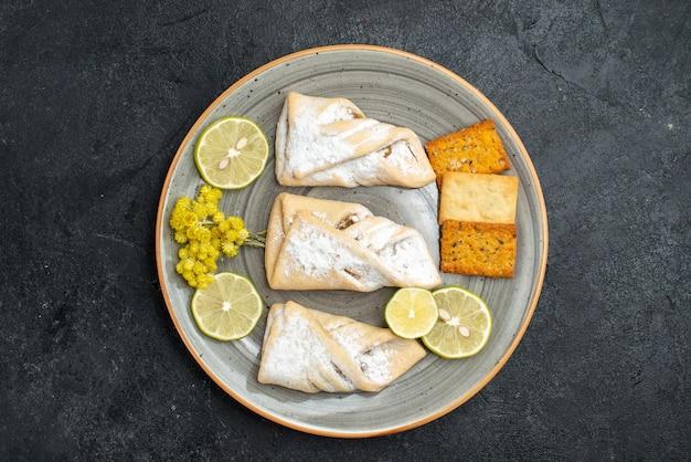 Draufsicht köstlicher teig mit zuckerpulver und crackern auf dunkelgrauem hintergrundgebäck backen zucker süßer kuchenplätzchen