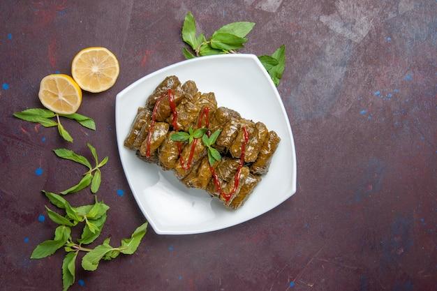 Draufsicht köstliches blatt-dolma-fleischgericht im teller auf dunklem schreibtisch