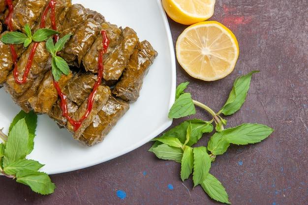 Draufsicht köstliches blatt-dolma-fleischgericht innerhalb der platte auf dunklem hintergrundtellerblatt-abendessen-essensfleisch