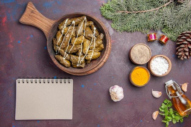 Draufsicht köstliches blatt-dolma-fleischgericht mit verschiedenen gewürzen auf dunklem hintergrund