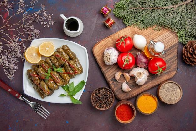 Draufsicht köstliches blatt-dolma mit frischem gemüse und gewürzen auf dem dunklen hintergrund-mahlzeitgericht blattfleisch-abendessen-essen