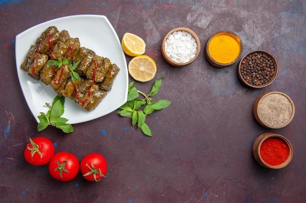 Draufsicht köstliches blatt-dolma mit zitronengewürzen und tomaten auf dem dunklen hintergrundtellerblatt-abendessen-essensfleisch