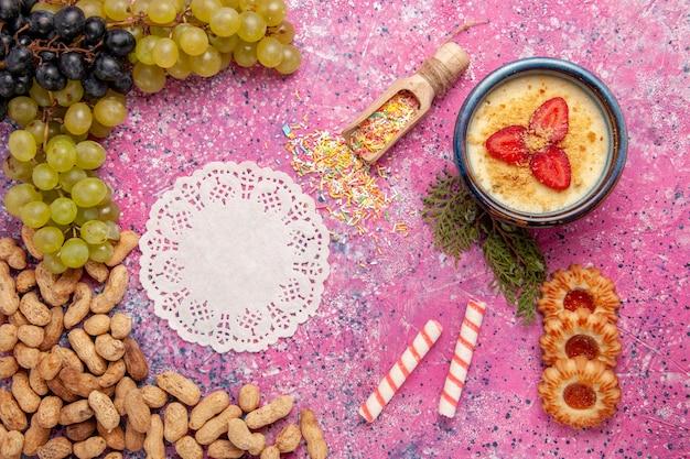 Draufsicht köstliches cremiges dessert mit frischen trauben, keksen, crackern und erdnüssen auf hellrosa oberflächen-dessert-eisbeerencreme-süßen früchten