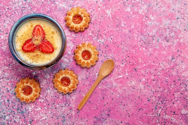 Draufsicht köstliches cremiges dessert mit rot geschnittenen erdbeeren und keksen auf dem rosa hintergrunddessert-eiscremefarbe süßes eis