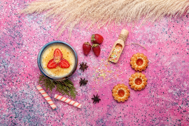 Draufsicht köstliches cremiges dessert mit rot geschnittenen erdbeeren und keksen auf hellrosa hintergrunddessert-eiscreme-beerenfrucht