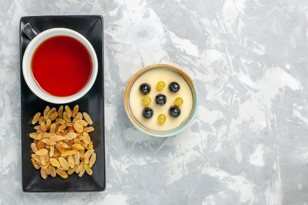 Draufsicht köstliches cremiges dessert mit tasse tee und rosinen auf weißem oberflächenfruchtcreme-desserteis-eis süßes eis