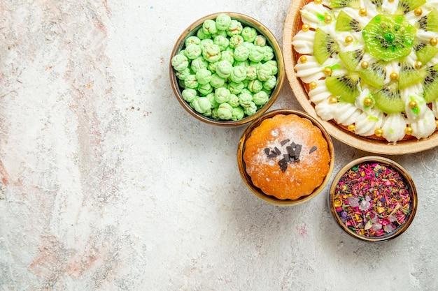 Draufsicht köstliches dessert mit geschnittenen kiwis und bonbons auf weißem hintergrund kuchen keks dessert sahne fruchtsüßigkeit