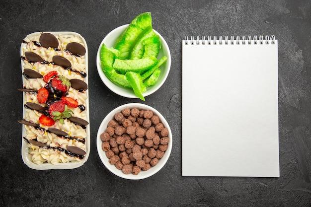 Draufsicht köstliches dessert mit schokoladenkeksen und erdbeeren auf dunklem hintergrund nusskeks süße fruchtbeerenkekse