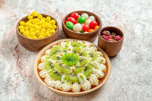 Draufsicht köstliches dessert mit weißer sahne und bonbons auf weißem hintergrund dessert sahnekuchen obst