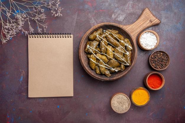 Draufsicht köstliches dolma-fleischgericht mit verschiedenen gewürzen auf dunklem schreibtischessen abendessengericht fleischkalorien