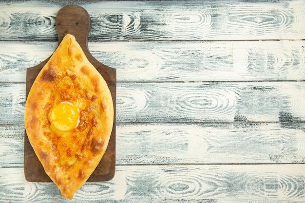 Draufsicht köstliches eierbrot, das auf grauem rustikalem raum gebacken wird