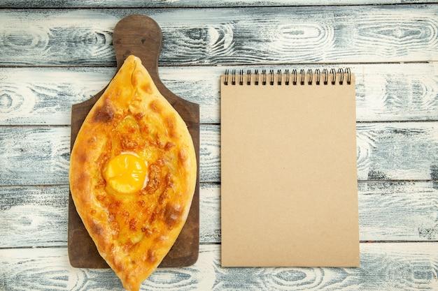 Draufsicht köstliches eierbrot, das auf grauem rustikalem schreibtisch gebacken wird