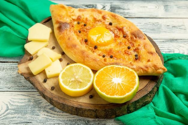 Draufsicht köstliches eierbrot, das mit käse auf einem rustikalen grauen schreibtisch gebacken wird