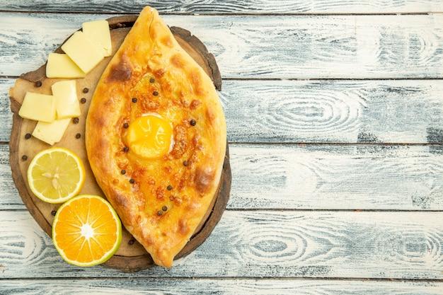 Draufsicht köstliches eierbrot, das mit käse auf rustikalem schreibtisch gebacken wird