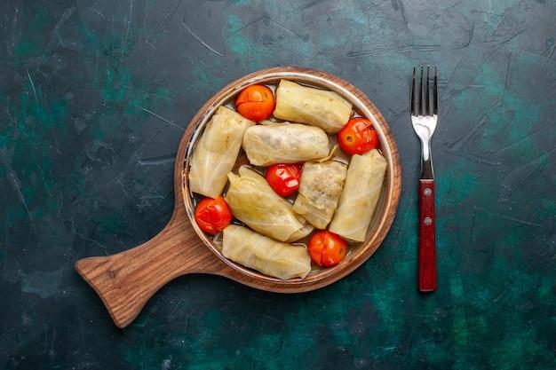 Draufsicht köstliches fleischmehl, das in kohl mit tomaten auf dunkelblauem boden gerollt wird fleischnahrungsmittelabendessenkaloriengemüsegeschirrkochen