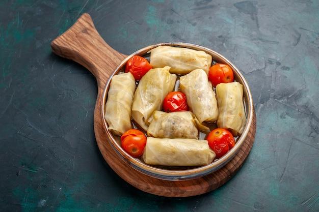 Draufsicht köstliches fleischmehl, das in kohl mit tomaten auf dunkelblauer oberfläche gerollt wird fleischnahrungsmittelabendessenkaloriengemüsegericht, das kocht