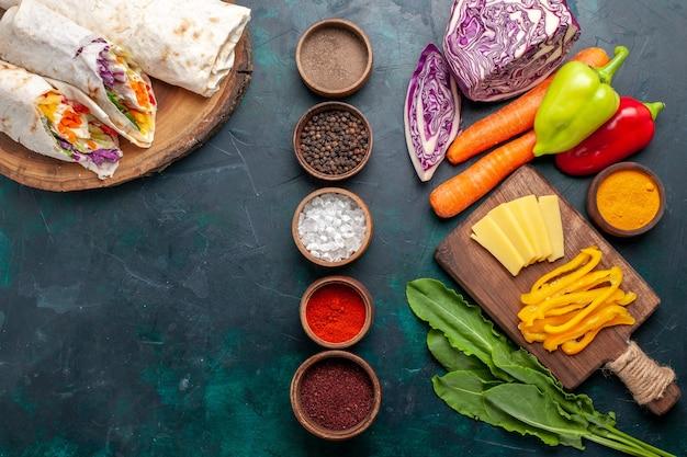 Draufsicht köstliches fleischsandwich aus fleisch am spieß mit gemüse und gewürzen auf blauem schreibtisch burger fleischmahlzeit mittagessen essen sandwich gegrillt