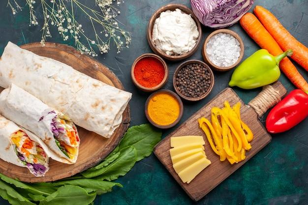 Draufsicht köstliches fleischsandwich aus fleisch am spieß mit gemüse und gewürzen auf blauem schreibtisch sandwich burger fleisch foto mahlzeit mittagessen essen gegrillt