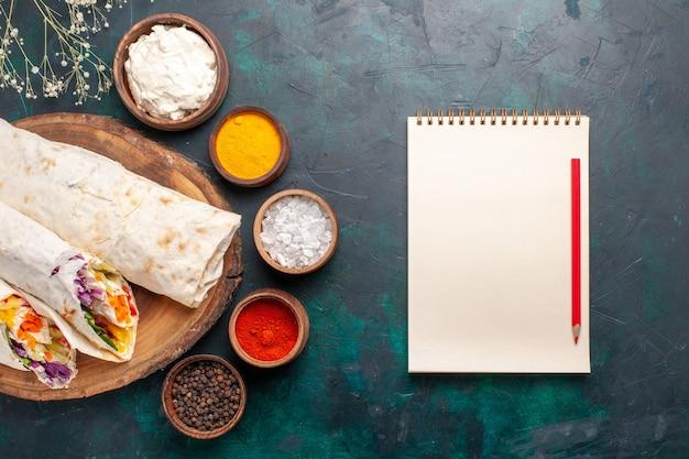 Draufsicht köstliches fleischsandwich aus fleisch am spieß mit gewürzen auf dem blauen hintergrund sandwich burger fleisch mahlzeit mittagessen essen gegrillt