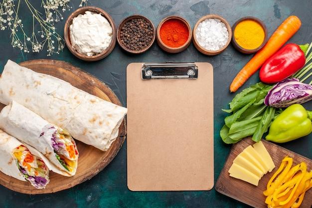 Draufsicht köstliches fleischsandwich aus fleisch am spieß mit gewürzen und gemüse auf dem blauen schreibtisch sandwich burger fleisch essen mahlzeit mittagessen gegrillt