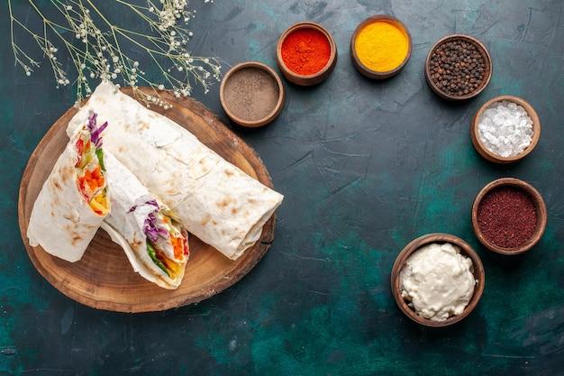 Draufsicht köstliches fleischsandwich aus fleisch gegrillt auf einem mit gewürzen geschnittenen spieß auf dem blauen schreibtisch burger fleischmahlzeit mittagssandwich