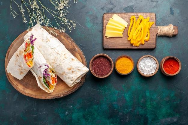 Draufsicht köstliches fleischsandwich aus fleisch, gegrillt auf einem mit gewürzen und käse geschnittenen spieß auf blauem schreibtisch burgerfleischmahlzeit-mittagssandwich