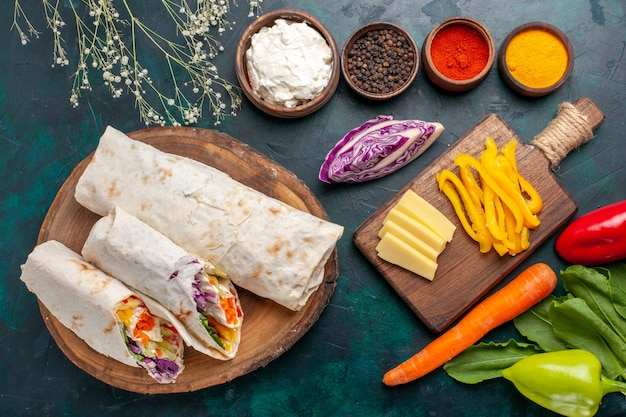 Draufsicht köstliches fleischsandwich ein sandwich aus fleisch am spieß mit gewürzen auf blauem schreibtisch sandwich burger fleisch essen mahlzeit mittagessen gegrillt