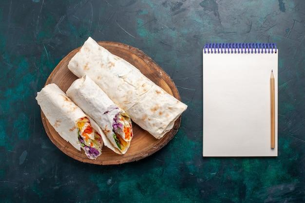 Draufsicht köstliches fleischsandwich ein sandwich aus fleisch, das auf einem spieß gegrillt wird, der auf dunkelblauem schreibtisch-sandwich-burger-essen-mahlzeit-mittagsfleisch geschnitten wird