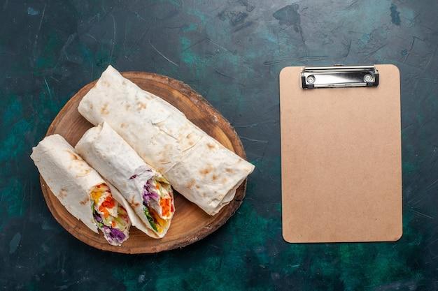 Draufsicht köstliches fleischsandwich ein sandwich gemacht vom fleisch, das auf einem spieß gegrillt wird, der auf dunkelblauem schreibtischsandwich-burger-nahrungsmittelmahlzeit-mittagsfleischfoto geschnitten wird