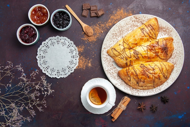 Draufsicht köstliches gebackenes gebäck mit tasse teemarmelade auf dunklem raum