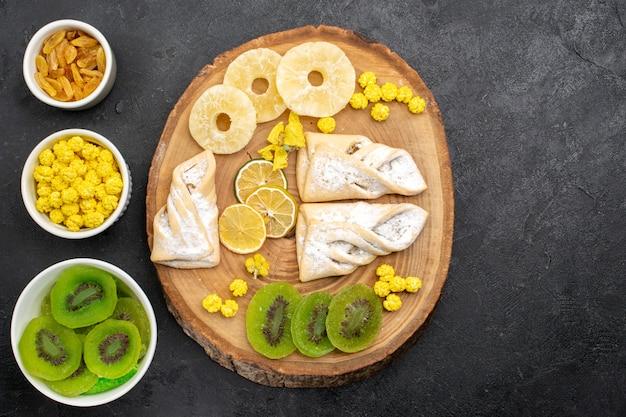 Draufsicht köstliches gebäck mit getrockneten ananasringen und kiwis auf grauem schreibtisch