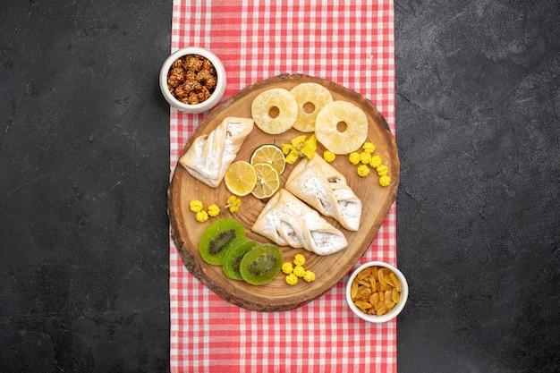 Draufsicht köstliches gebäck mit getrockneten ananasringen und kiwis auf grauzone