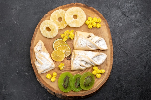 Draufsicht köstliches gebäck mit getrockneten fruchtscheiben auf der grauzone