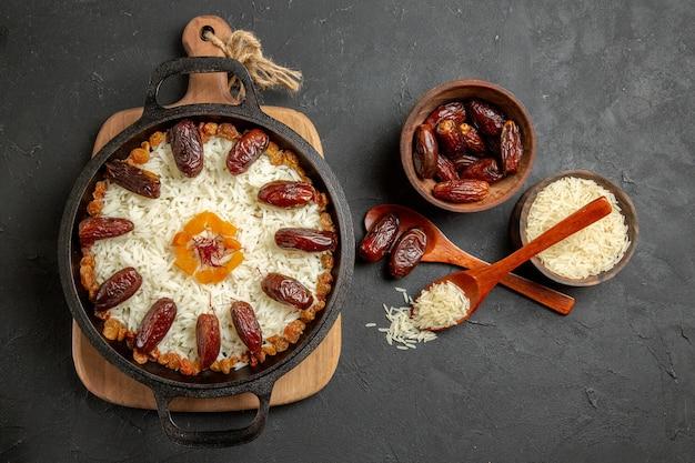 Draufsicht köstliches gekochtes plov-reismahl mit khurma auf dunkler oberfläche plov-reis-kochgericht