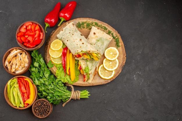 Draufsicht köstliches geschnittenes shaurma-fleisch-sandwich mit zitrone und grüns auf dunklem hintergrund burger-sandwich reifes snack-brot