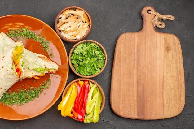 Draufsicht köstliches geschnittenes shaurma-salat-sandwich mit grüns auf dunkelviolettem hintergrund burger-mahlzeit-sandwich-brot-snack