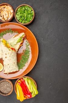 Draufsicht köstliches geschnittenes shaurma-salat-sandwich mit grüns auf dunklem hintergrund burger-mahlzeit-brot-snack-sandwich