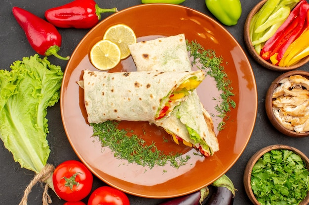 Draufsicht köstliches geschnittenes shaurma-sandwich mit gemüse und grüns auf dunklem hintergrund burger-mahlzeit-sandwich-snack-brot