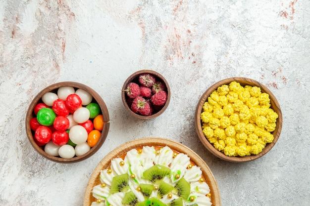 Draufsicht köstliches kiwi-dessert mit bonbons auf weißem hintergrund dessertkuchen sahnefruchtsüßigkeit