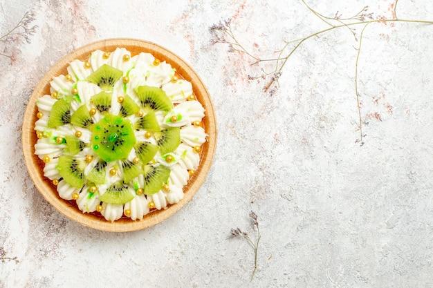 Draufsicht köstliches kiwi-dessert mit leckerer weißer sahne und geschnittenen früchten auf weißem hintergrund dessertkuchen sahnefrucht tropisch