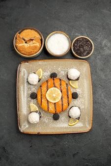 Draufsicht köstliches kuchendessert mit kokosbonbons auf dem dunklen oberflächenkuchendessert süßer kuchensüßigkeitstee